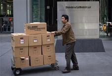 A man moves boxes out of the offices of Dewey & LeBoeuf in New York May 11, 2012. Once one of the largest law firms in the United States, Dewey & LeBoeuf has suffered a wave of partner defections in recent months amid a debt crisis and concerns over partner compensation. REUTERS/Eduardo Munoz