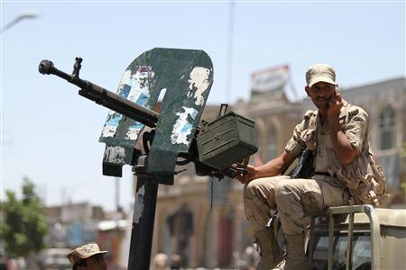 A defected army soldier, backing anti-government protesters, talks on his mobile phone as he mans a machine gun atop a military vehicle securing a road where protesters are holding a rally and the weekly Friday prayers in Sanaa May 18, 2012. REUTERS/Mohamed al-Sayaghi