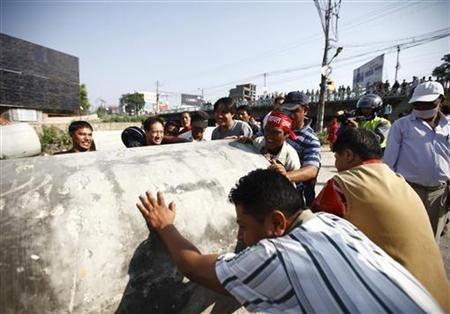Protesters use a drainage pipe to obstruct the road during a three-day general strike called by the Nepal Federation of Indigenous Nationalities (NEFIN) in Kathmandu May 20, 2012. REUTERS/Navesh Chitrakar