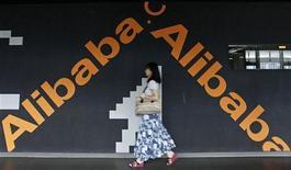 Женщина проходит мимо стены с логотипами Alibaba Technology Co. Ltd в здании офиса компании в Ханчжоу, 21 мая 2011 года. Yahoo Inc продаст половину свой доли в китайской группе Alibaba за $7,1 миллиарда и распределит основную часть полученных средств между акционерами, сообщила американская интернет-компания. REUTERS/Steven Shi
