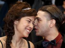 "Actress Mylene Jampanoi (L) and director Xavier Dolan arrive on the red carpet ahead of the screening of the film ""Amour"", by director Michael Haneke in competition at the 65th Cannes Film Festival, May 20, 2012. REUTERS/Christian Hartmann"