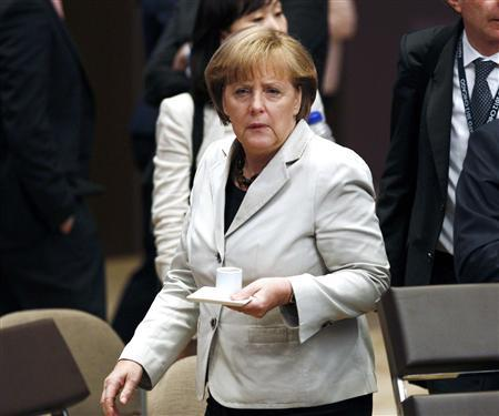 German Chancellor Angela Merkel carries a coffee to her seat at the 2012 NATO Summit in Chicago, May 21, 2012. REUTERS/Jim Young