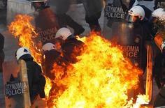 Греческие полицейские после взрыва коктейля Молотова во время акций протеста в Афинах 12 февраля 2012 года. Соединенные Штаты и Япония возглавляют хрупкое экономическое восстановление развитых стран, которое еще может отклониться от курса, если еврозона не сможет сдержать нарастающий кризис, заявила во вторник Организация экономического сотрудничества и развития. REUTERS/Yannis Behrakis