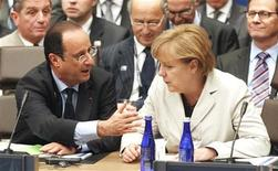 German Chancellor Angela Merkel (R) listens to French President Francois Hollande during the 2012 NATO Summit in Chicago, May 21, 2012. REUTERS/Jeff Haynes