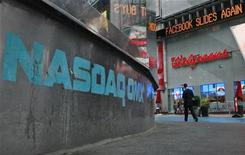 Manchete sobre as ações do Facebook é vista no Times Square Newsticker ao fundo do logo do Nasdaq em Nova York. As ações do Facebook caíam nesta terça-feira, à medida que investidores continuavam a questionar o valor dos papéis após a Reuters ter noticiado que bancos coordenadores cortaram suas previsões de receita para a companhia pouco antes da oferta pública inicial de ações da rede social. 22/04/2012 REUTERS/Brendan McDermid
