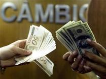 """Um brasileiro troca reais por dólares numa casa de câmbio no centro do Rio de Janeiro, 4 de agosto de 2003. O ministro do Desenvolvimento, Indústria e Comércio Exterior, Fernando Pimentel, afirmou nesta terça-feira que a recente alta do dólar é """"preocupante"""" para as importações. REUTERS/Bruno Domingos"""