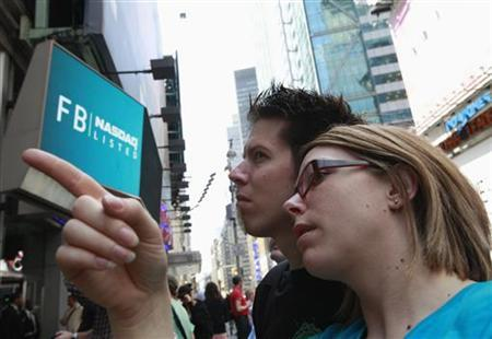 People gather outside the NASDAQ Marketsite waiting to see Facebook's share prices posted inside on video monitors in New York May 18, 2012. REUTERS/Brendan McDermid