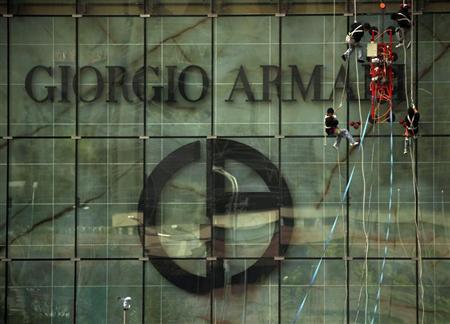 Cleaners abseil down the front of a shopping mall displaying the logo of Italian fashion label Giorgio Armani in central Beijing June 26, 2011. REUTERS/David Gray