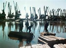 Дети катаются на досках во время паводка в порту Дудинка 30 мая 1999 года. Норильский никель, крупнейший в мире производитель никеля и палладия, остановил работу ключевого порта Дудинка в Арктике из-за сезонного паводка. REUTERS/Str Old