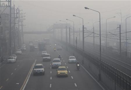 Motorists switch on their headlights while crossing a highway covered by smog in Manila January 1, 2012. REUTERS/Romeo Ranoco