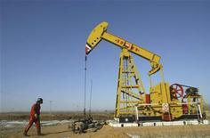 Рабочий проходит мимо станка-качалки на заводе PetroChina в окрестностях Шэньяня 13 января 2008 года. Цены на нефть растут, так как сообщения о проблемах в переговорах с Ираном о ядерной программе компенсируют слабую статистику Китая и Европы. REUTERS/Stringer