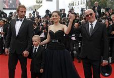 """Director Audiard (R) arrives on the red carpet with cast members Matthias Schoenaerts (L), Armand Verdure (2ndL) and Marion Cotillard for the screening of the film """"De rouille et d'os"""", in competition at the 65th Cannes Film Festival, May 17, 2012. REUTERS/Jean-Paul Pelissier"""