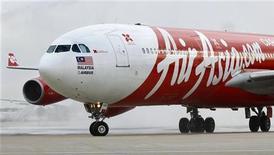 Самолет Airbus A340 авиакомпании AirAsia стоит на взлетной полосе в аэропорту в Париже, 06 июля 2011 года. AirAsia изучает потенциальную $4-миллиардную сделку по покупке еще 50 пассажирских самолетов Airbus A320, сказал Рейтер основатель компании. REUTERS/Charles Platiau/Files