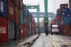 """Мужчина проходит мимо грузовых контейнеров в порту в Шанхае, 10 февраля 2011 года. Рост экспорта и импорта КНР показал признаки ускорения за первые 10 дней мая, но обстановка для внешней торговли в КНР все еще """"довольно жесткая"""", сообщило в пятницу министерство торговли страны. REUTERS/Aly Song"""