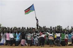 A man holds up South Sudan's new flag as South Sudanese children rehearse a dance routine ahead of a soccer match between South Sudan and Kenya as part of the independence day celebrations, July 7, 2011. REUTERS/Paul Banks/UNMIS/Handout