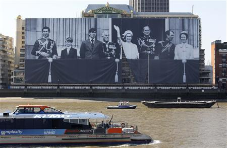 Abseilers secure a giant canvas along the River Thames of a photograph showing Britain's Royal Family during the 1977 Silver Jubilee, London May 25, 2012. REUTERS/Suzanne Plunkett
