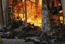 Пожар в магазине одежды после взрыва в торговом центре в Найроби 28 мая 2012 года. Мощный взрыв сотряс столицу Кении в понедельник: на кадрах телетрансляции видно, как сильно поврежденное здание торгового центра в Найроби охвачено огнем, а покидающие место происшествия люди уносят несколько раненых. REUTERS/Johnson Mugo