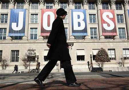 A woman walks past a ''Jobs'' banner hung above the Chamber of Commerce in Washington February 6, 2012. REUTERS/Kevin Lamarque