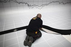 A graph is seen above a worker as he puts the finishing touches to a stage decoration for an investment funds awards dinner at the Madrid stock exchange May 17, 2012. REUTERS/Paul Hanna