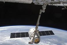 Com a Terra ao fundo, a nave cargueira comercial SpaceX Dragon é vista sendo manipulada por braço robótico da Estação Espacial Internacional em imagem de divulgação da NASA. Astronautas a bordo da Estação Espacial Internacional liberaram a nave Dragon para voltar à Terra. 25/05/2012 REUTERS/NASA/Divulgação