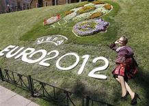 Женщина позирует у клумбы с логотипом Евро-2012 в Киеве 8 июня 2010 года. Правительство Украины объявило выходными дни матчей чемпионата Европы по футболу в принимающих городах и обязало Киев, Донецк, Львов и Харьков отработать их в последующие субботы. REUTERS/Gleb Garanich