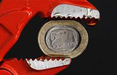 Монета в 1 евро зажата в тисках. Фотография сделана в Афинах 20 октября 2011 года. Евро остается вблизи двухлетнего минимума к доллару и одиннадцатилетнего минимума к иене из-за волнений по поводу банковского сектора Испании. REUTERS/Yiorgos Karahalis