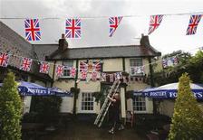 Pub landlord Scott Green hangs Union flag bunting across The Jubilee pub ahead of Britain Queen Elizabeth's diamond jubilee celebrations in Sunbury-on-Thames in south west London May 30, 2012. REUTERS/Luke MacGregor