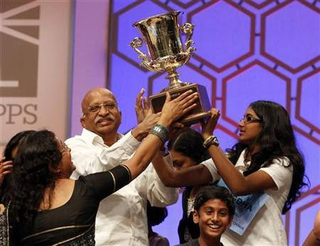 Snigdha Nandipati (R), 14, of San Diego, California, holds her trophy along with family members after winning the Scripps National Spelling Bee at National Harbor in Maryland May 31, 2012. REUTERS/Kevin Lamarque