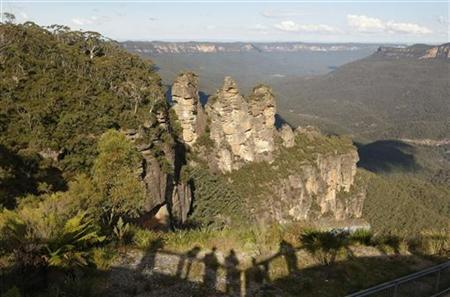 Tourists cast shadows as they view a sandstone cliff outcrop known as ''The Three Sisters'' (L) from Echo Point in the Blue Mountains town of Katoomba, about 90 kilometres (56 miles) west of Sydney May 17, 2008. REUTERS/Tim Wimborne