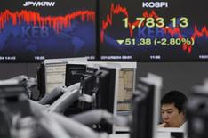 A currency dealer works in front of a screen showing the current Korea Composite Stock Price Index (KOSPI) (R) at a dealing room of a bank in Seoul June 4, 2012. REUTERS/Kim Hong-Ji