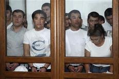 Обвиняемые по делу о беспорядках в Жанаозене в декабре 2011 года сидят в камере в зале суда в Актау 4 июня 2012 года. Суд в Казахстане осудил более 30 нефтяников за беспорядки в Жанаозене, кровавое подавление которых в декабре прошлого года подорвало имидж стабильного государства. REUTERS/Olga Yaroslavskaya