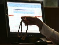 Саудовский трейдер держит четки во время работы в Саудовском инвестиционном банке в Эр-Рияде, 18 марта 2008 г. Суд Кувейта приговорил в понедельник Хамада аль-Наки к 10 годам тюрьмы за оскорбительные комментарии о пророке Мохаммеде и суннитских правителях Саудовской Аравии и Бахрейна в социальных сетях, сообщил адвокат осужденного. REUTERS/Stringer