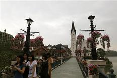 Women walk at the Chinese replica of Austria's UNESCO heritage site, Hallstatt village in China's southern city of Huizhou in Guangdong province June 2, 2012. Metals and mining company China Minmetals Corporation spent $940 million to build this controversial site and hopes to attract both tourists and property investors alike, according to local newspaper reports. REUTERS/Tyrone Siu