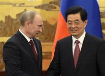 Президент России Владимир Путин и китайский лидер Ху Цзиньтао обмениваются рукопожатием на встрече в Пекине 5 июня 2012. Китай провозгласил единую с Россией позицию противодействовать иностранной интервенции или принудительной смене режима в Сирии, настаивая на воплощении дающего сбои мирного плана спецпредставителя ООН Кофи Аннана. REUTERS/Mark Ralston/Pool