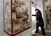 Пожертвованные на благотворительность белорусские рубли в магазине в Минске, 15 февраля 2012 года. Белоруссия, переживающая последствия самого тяжелого за десятилетие финансового кризиса, надеется в октябре вернуться к переговорам с МВФ о новом кредите и обещает придерживаться жесткой макроэкономической политики с медленным снижением процентных ставок, соответствующим замедлению инфляции. REUTERS/Vasily Fedosenko