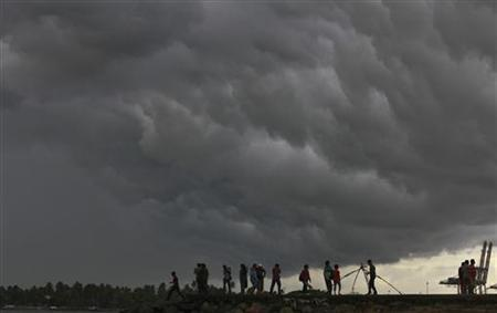 People stand on a seaside promenade against the background of pre-monsoon clouds gathered over the Arabian Sea at Kochi in Kerala June 4, 2012. REUTERS/Sivaram V