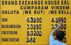 Мужчина меняет цифры на табло с курсами валют в Бухаресте, 30 апреля 2012 года. Евро вырос в среду благодаря закрытию коротких позиций после того, как рискованные активы укрепились на сильных данных об экономическом росте в Австралии. REUTERS/Bogdan Cristel