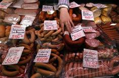 Продавец торгует когбасами и сосисками на городском рынке в Санкт-Петербурге 5 апреля 2012 года. Инфляция в РФ замедлилась за период с 29 мая по 4 июня до 0,1 процента с 0,2 процента неделей ранее, сообщил Росстат. REUTERS/Alexander Demianchuk