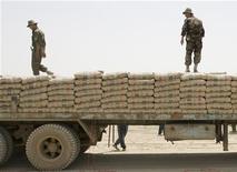 Таджикские пограничники ходят по мешкам с цементом на грузовиек, прибывшем из Афганистана в погранпункт Панджи Поён 31 мая 2008. Китай выступил участником строительства в Таджикистане второго и в 10 раз более мощного цементного завода - $600-миллионного проекта, к которому на фоне спроса на стройматериалы вы регионе присматривался Иран. REUTERS/Shamil Zhumatov