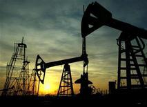 Станки-качалки на нефтяном месторождении в Баку на фоне встающего солнца 16 октября 2005 года. Активы Госнефтекомпании Азербайджана (ГНКАР) достигли 17 миллиардов манатов (свыше $21 миллиарда) к началу 2012 года, увеличившись за последние четыре года на 36 процентов, сказал вице-президент ГНКАР Сулейман Гасымов. REUTERS/David Mdzinarishvili