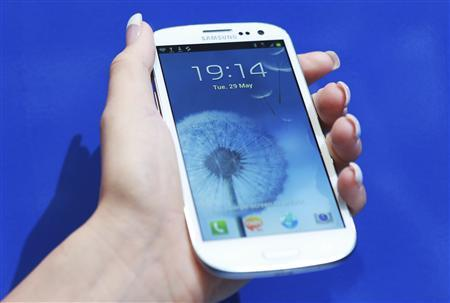 A woman holds her new Samsung Galaxy S III after it was launched at Westfield in London in this file photo taken May 29, 2012. REUTERS/Olivia Harris/Files