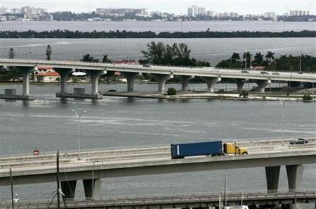 A truck transports a container into a port of Miami, October 4, 2007. REUTERS/Carlos Barria/Files