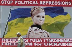 Homem caminha em frente a quadro com retrato da ex-primeira-ministra da Ucrânia e líder da oposição, Yulia Tymoshenko, que está presa, no centro de Kiev. 01/06/2012 REUTERS/Gleb Garanich