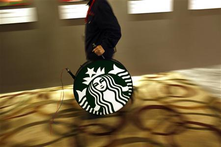 A man carries a Starbucks logo sign after a corporate event at a hotel in Shanghai April 19, 2012. Starbucks Corp wants to make its mainland China expansion a family affair. The world's biggest coffee chain is opening cafes in China at a rate of one every four days in its quest to expand from about 570 shops today to more than 1,500 by 2015. REUTERS/Carlos Barria