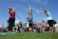People take part in a free weekly yoga class on the front lawn of Parliament Hill in Ottawa August 17, 2011. REUTERS/Chris Wattie