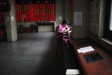 An investor looks at computer screens showing stock information at a brokerage house in Shanghai June 8, 2012. REUTERS/Aly Song