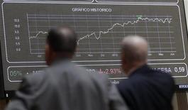 Трейдеры смотрят на электронное табло с динамикой котировок на фондовой бирже в Мадриде 12 июня 2012 года. Европейские акции снижаются на фоне проблем еврозоны и накануне выборов в Греции. REUTERS/Andrea Comas
