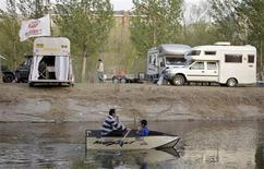 A man rows a boat carrying a child on a lake in front of recreational vehicles (RV), during a camping trip at a RV park on the outskirts of Beijing, April 14, 2012. REUTERS/Soo Hoo Zheyang
