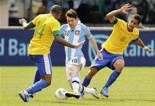 O argentino Lionel Messi passa entre os brasileiros Rômulo e Juan em amistoso disputado no sábado. REUTERS/Eduardo Munoz