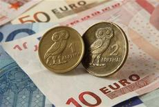 Монеты выведенной из оборота греческой драхмы на фоне банкнот евро. Фотография сделана в Стамбуле 14 июня 2012 года. Крупнейшие центробанки мира готовы принять меры, включая скоординированные действия, для стабилизации рынков, в то время как мировые экономики готовятся к возможному финансовому шторму после ключевых выборов Греции в эти выходные. REUTERS/Murad Sezer
